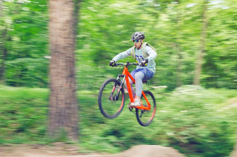 Cyclist in helmet on an orange bike doing a trick in a springboard jump in the forest, motion blur royalty free stock photography