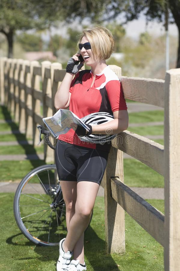 Cyclist with her bike leaning on fence while using cell phone. Happy female cyclist with bicycle holding roadmap using cell phone while leaning on fence stock images