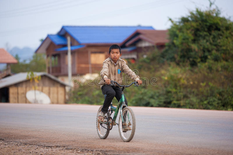 Cyclist in Laos. Three Children A biker is cycling returning home from the school in Thakhek, Laos royalty free stock image