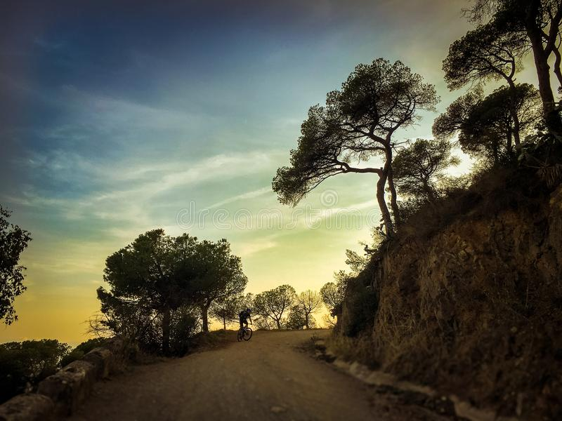 Cyclist man riding a mountain bike at sunset mountain tibidabo in Spain city of Barcelona stock photography