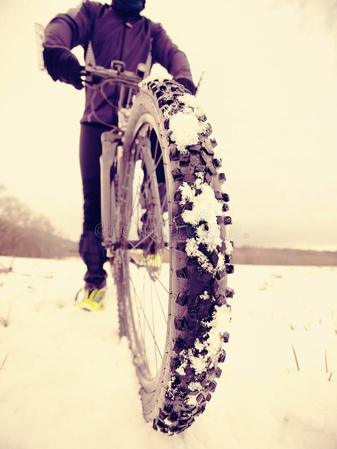 Cyclist man with winter bike stays in snow. Winter extreme sportive concept. Cyclist man with winter bike stays in snow. Winter extreme sport, sportive concept stock photo