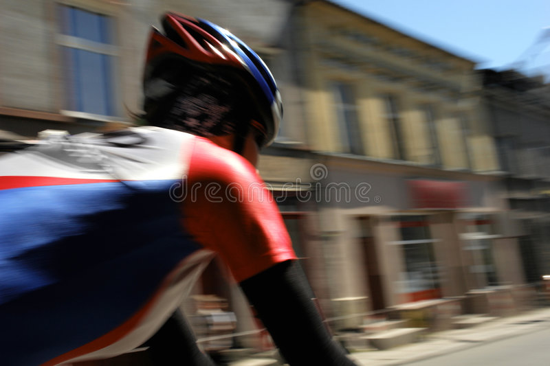 Cyclist in Motion. Motion blur image of helmeted cyclist riding through urban street scene royalty free stock photo