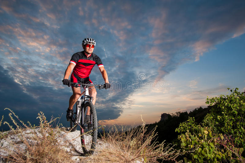 Cyclist on mountain bike races downhill in the nature. Happy man on a mountain bike races downhill in the nature against blue cloudy evening sky. Cyclist is royalty free stock photo