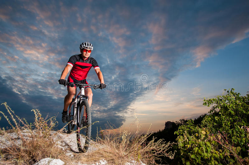 Cyclist on mountain bike races downhill in the nature. Happy man on a mountain bike races downhill in the nature against blue cloudy evening sky. Cyclist is stock images