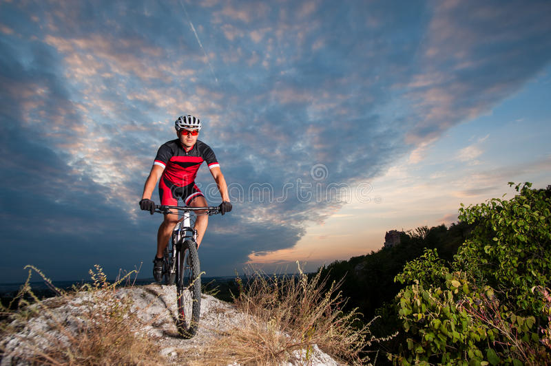 Cyclist on mountain bike races downhill in the nature. Happy man on a mountain bike races downhill in the nature against blue cloudy evening sky. Cyclist is royalty free stock photography
