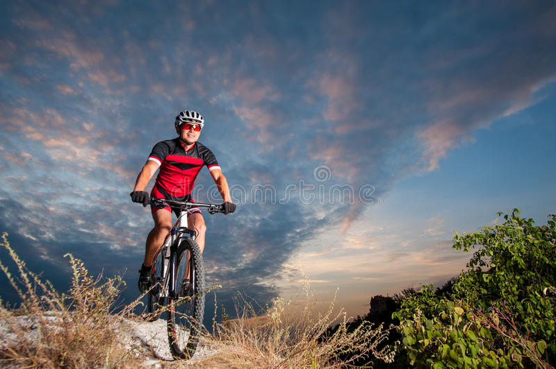 Cyclist on mountain bike races downhill in the nature. Happy man on a mountain bike races downhill in the nature against blue cloudy evening sky. Cyclist is stock image