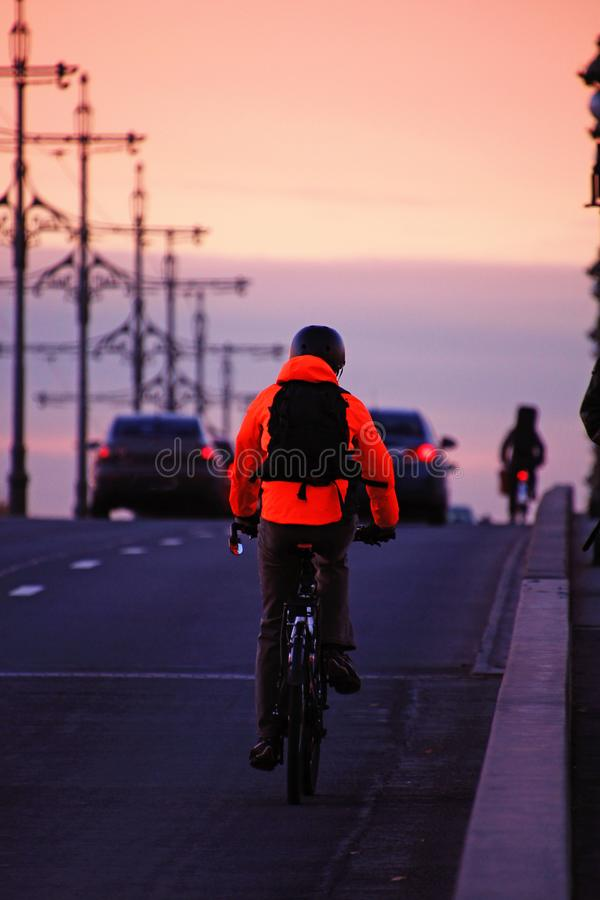 Cyclist in an orange jacket with a backpack royalty free stock photos