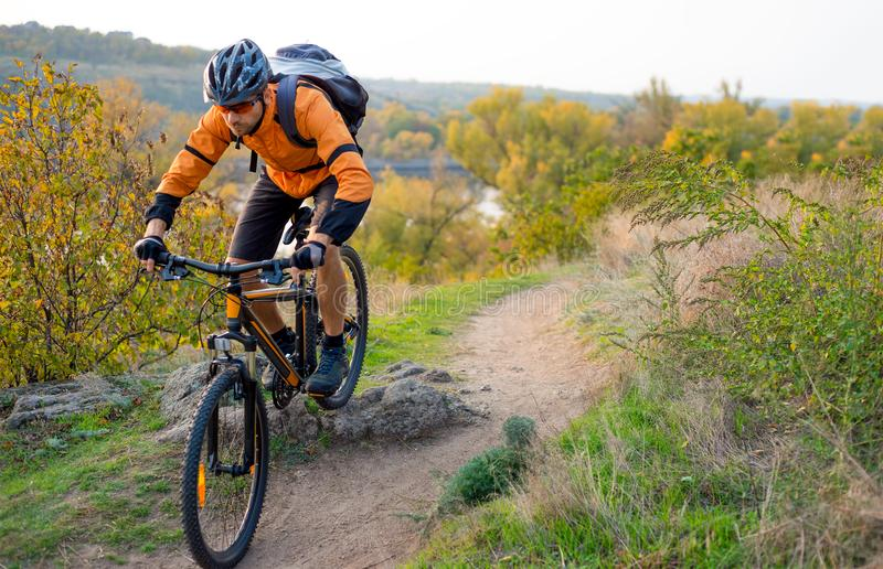 Cyclist in Orange Riding the Mountain Bike on the Autumn Rocky Trail. Extreme Sport and Enduro Biking Concept. Cyclist in Orange Riding the Mountain Bike on the royalty free stock photography