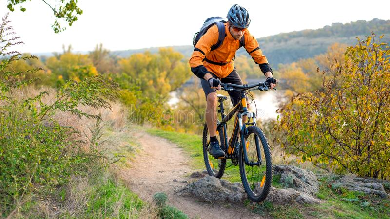 Cyclist in Orange Riding the Mountain Bike on the Autumn Rocky Trail. Extreme Sport and Enduro Biking Concept. Cyclist in Orange Riding the Mountain Bike on the