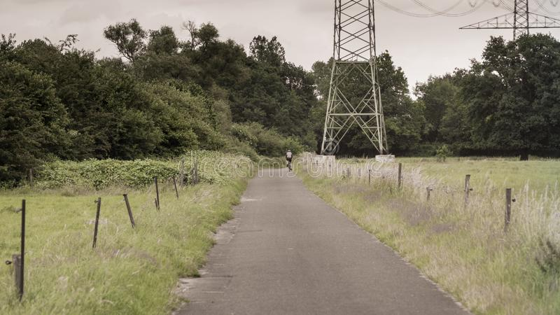 A cyclist passes a high voltage pylon on a road in the meadows. royalty free stock photos