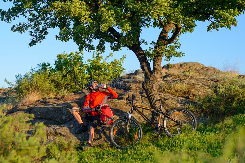 Cyclist in Red Jacket and Helmet Resting and Drinking the Water near Mountain Bike on Rocky Hill under Beautiful Green Tree. Adven. Cyclist in Red Jacket and stock images