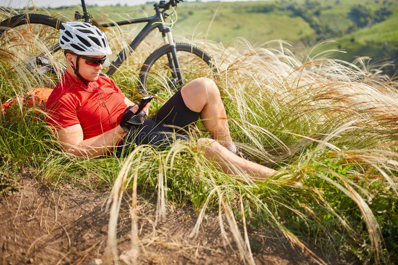Cyclist in Red Jacket and Helmet Resting near Mountain Bike on the Rocky Hill. Adventure and Travel Concept. Cyclist in Red Jacket and Helmet Resting near royalty free stock photos