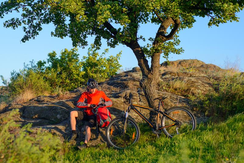 Cyclist in Red Jacket and Helmet Resting near Mountain Bike on Rocky Hill under Beautiful Green Tree. Adventure and Travel Concept. Cyclist in Red Jacket and stock photography