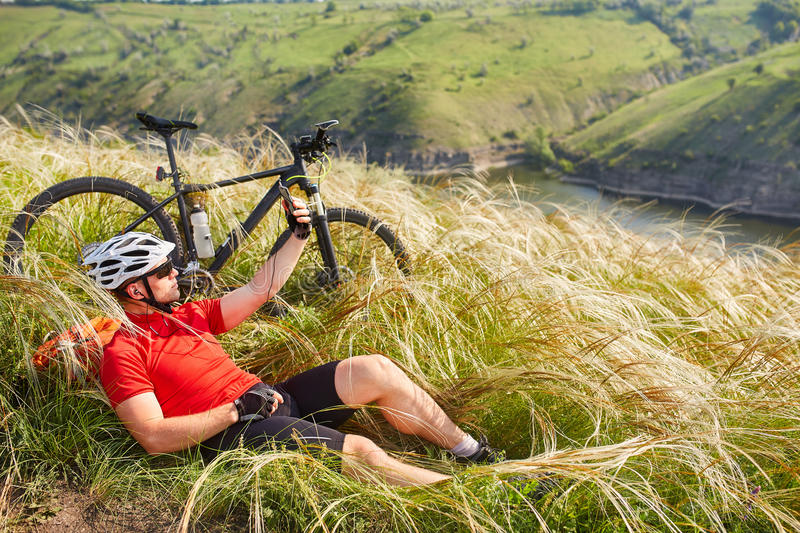 Cyclist in Red Jacket and Helmet Resting near Mountain Bike on the Rocky Hill. Adventure and Travel Concept. Cyclist in Red Jacket and Helmet Resting near royalty free stock image