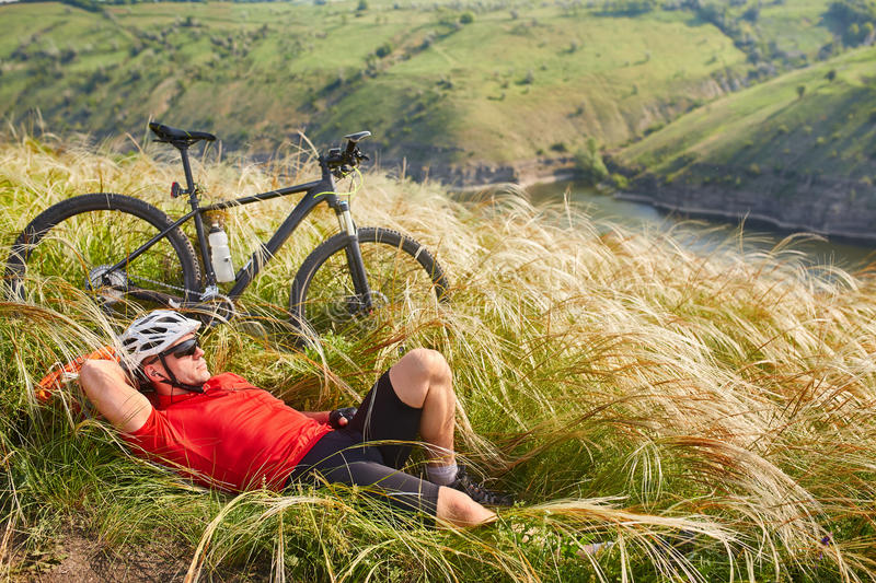 Cyclist in Red Jacket and Helmet Resting near Mountain Bike on the Rocky Hill. Adventure and Travel Concept. Cyclist in Red Jacket and Helmet Resting near stock images