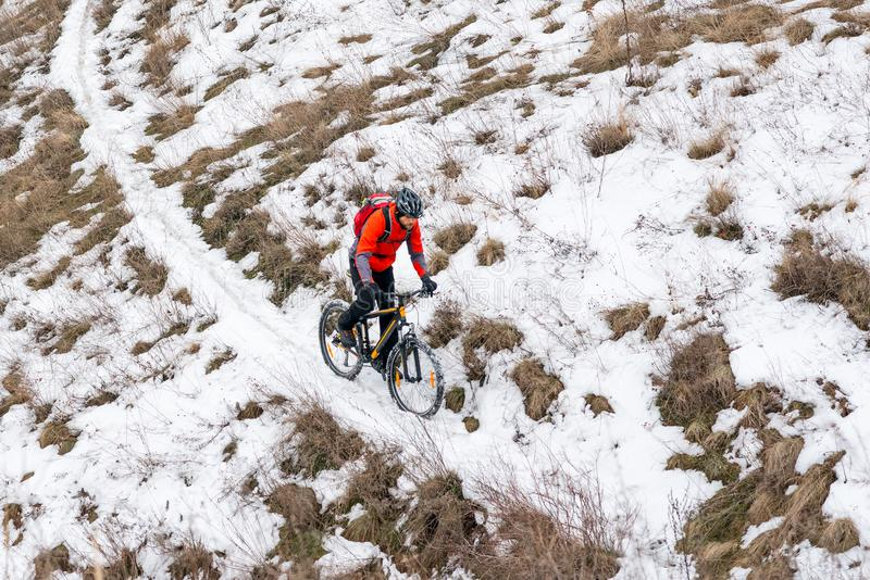Cyclist in Red Riding Mountain Bike on the Snowy Trail. Extreme Winter Sport and Enduro Biking Concept. Cyclist in Red Riding the Mountain Bike on the Snowy royalty free stock photography