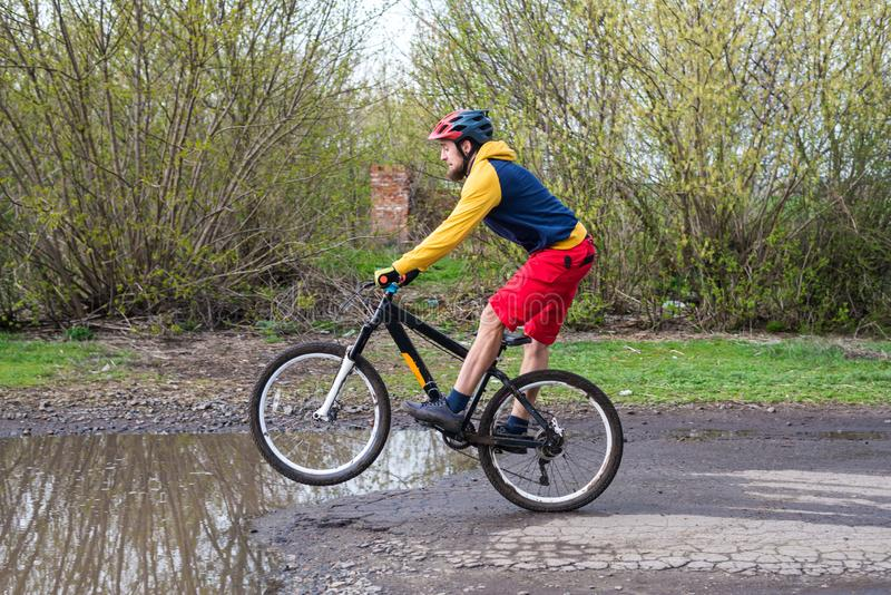A cyclist in red shorts and a yellow jacket riding a bicycle on the rear wheel through a puddle royalty free stock photo