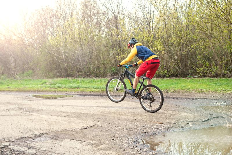 A cyclist in red shorts and a yellow jacket riding a bicycle on the rear wheel through a puddle stock photo