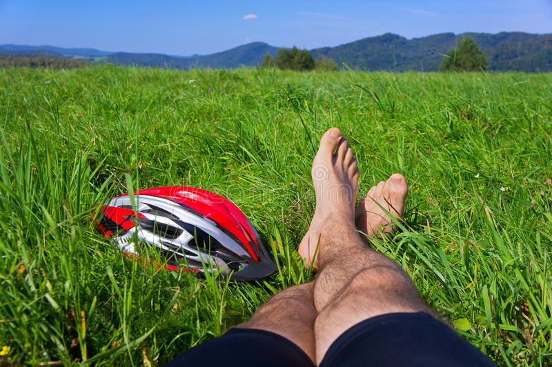 Cyclist relax on grass in mountains. stock photos