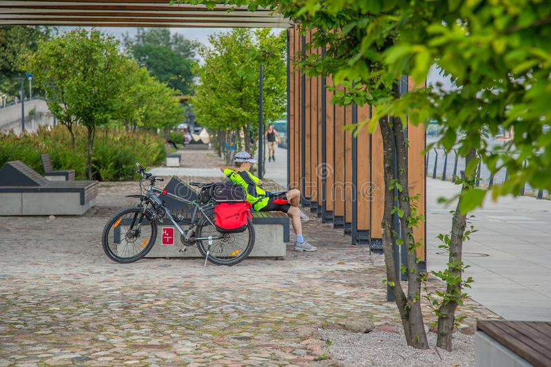 Cyclist resting on a bench on a walkway. Modern city, Cyclist resting on a bench on a walkway stock photos