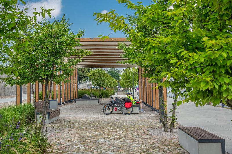 Cyclist resting on a bench on a walkway. Modern city, Cyclist resting on a bench on a walkway stock photo