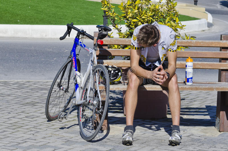 A cyclist resting. On a brown bench before preparing for the next milestone stock images