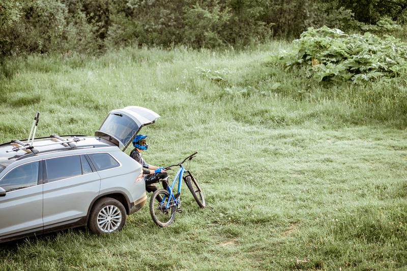 Cyclist resting in the car trunk. Professional cyclist resting with bicycle while sitting in the car trunk on the green meadow in the mountains. View from above royalty free stock photography