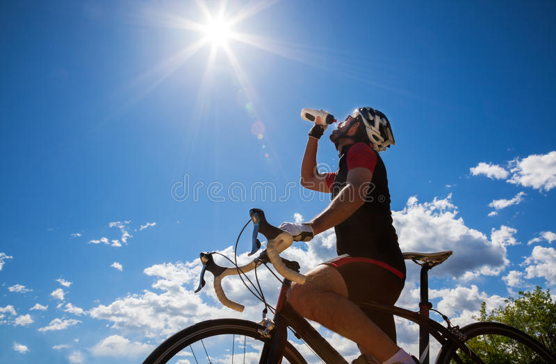 Cyclist resting and drinking isotonic drink. Backlight, sunny summer day royalty free stock photo
