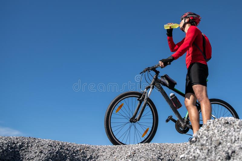 Cyclist resting and drinking isotonic drink. Backlight, sunny summer day. Extreme mountain bike sport athlete man riding outdoors stock images