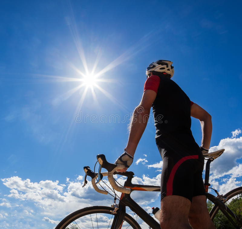 Cyclist resting and drinking isotonic drink. Road cyclist resting on his bike. Backlight, sunny summer day royalty free stock images