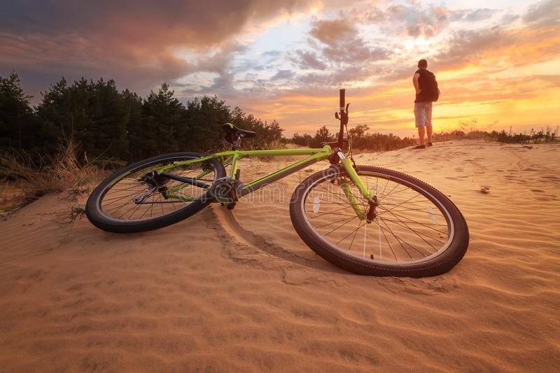 Cyclist resting while Hiking. / colorful sunset bright clouds royalty free stock photo