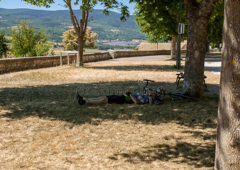 Cyclist resting in the shade of a tree in Sault. Provence, France. Sault, France - June 25, 2016: Cyclist resting in the shade of a tree in Sault. Provence stock photo