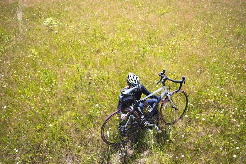 Cyclist resting from trip while sitting in meadow with grass and field flowers holding his bicycle. Cyclist who prefers a healthy lifestyle in sportswear and stock photography