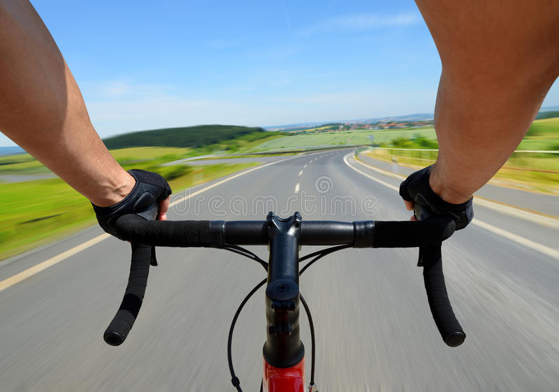Cyclist rides on a road bike. Hands in gloves holding handlebar. Cyclist rides on a road bike royalty free stock photos