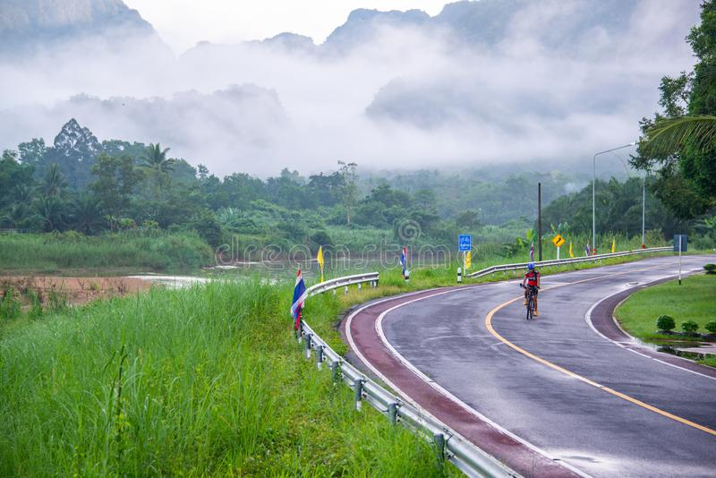 Cyclist riding bicycle on country road stock photos