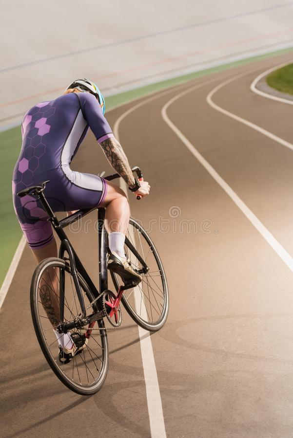 Cyclist riding bicycle on cycle race track. Back view of cyclist riding bicycle on cycle race track stock photo