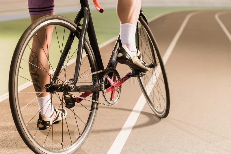 Cyclist riding bicycle on cycle race track. Partial view of cyclist riding bicycle on cycle race track stock photography