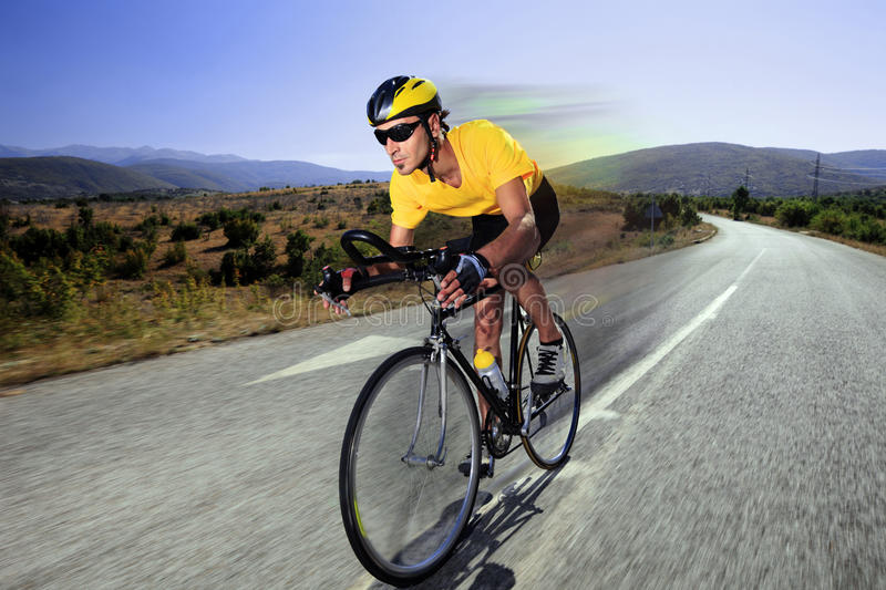 Cyclist riding a bike on an open road stock photos
