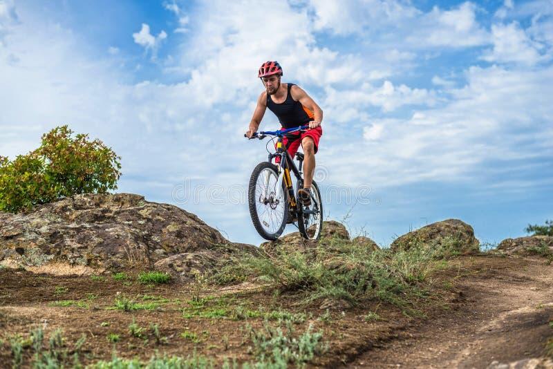 Cyclist riding down the rock on a mountain bike, extreme enduro cycling. stock photo