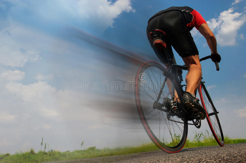 Cyclist riding fast on the asphalt road stock images