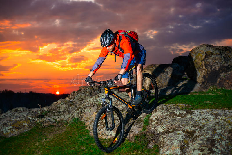 Cyclist Riding Mountain Bike Down Spring Rocky Hill At Beautiful