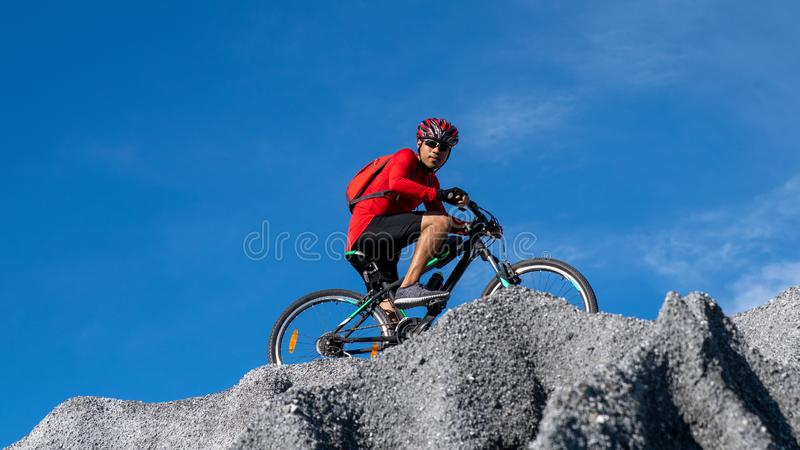 Cyclist riding mountain bike on the rocky trail at sunset. Extreme mountain bike sport athlete man riding outdoors lifestyle trail royalty free stock photography
