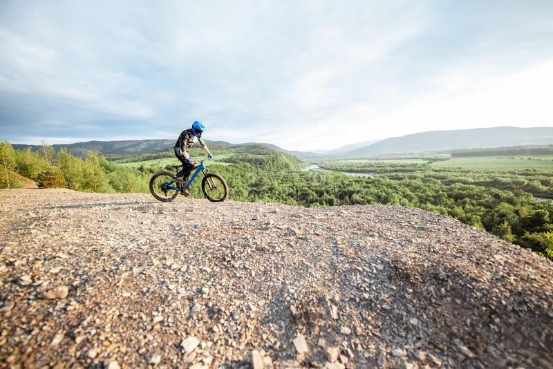 Cyclist riding on the rocky mountains royalty free stock photos