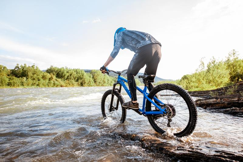 Cyclist riding on the rocky riverside stock photos