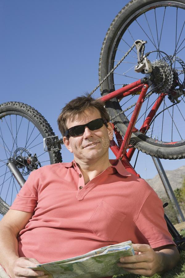 Cyclist With Roadmap Lying In Front Of Bicycle Upside Down. Happy male cyclist with roadmap lying in front of bicycle upside down against blue sky royalty free stock photos