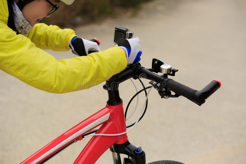 Cyclist setting active camera. Before riding mountain bike on forest trail stock photography