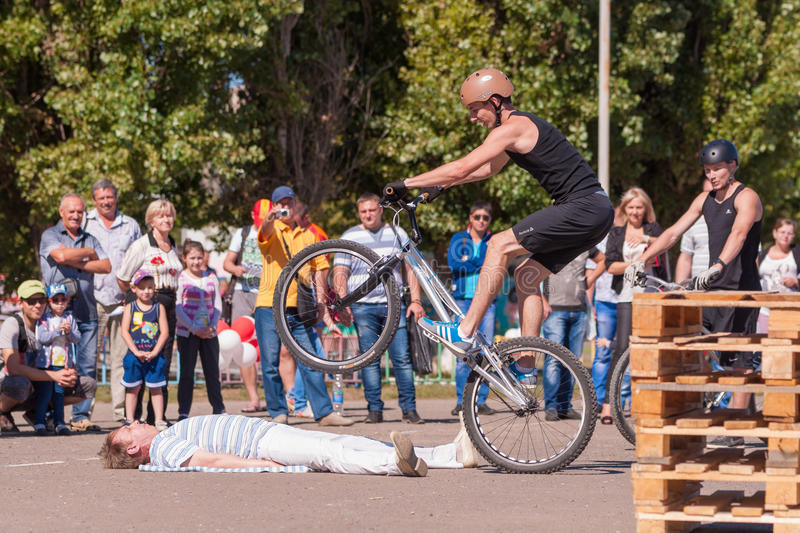 Cyclist shows viewers his professionalism in the management of a bicycle. Volgograd, Russia - September 6, 2014: Two cyclists ride of traceurs in the style of royalty free stock photo