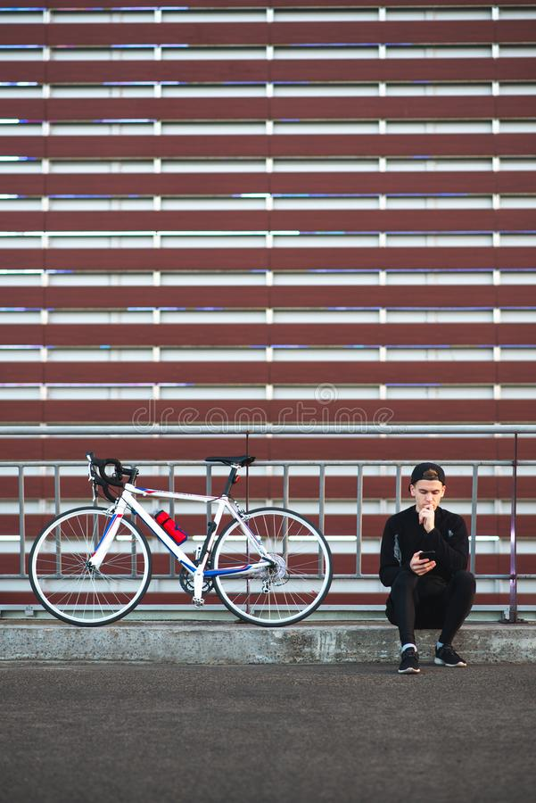 Cyclist sits on the background of the wall and uses a smartphone. Copyspace stock photos