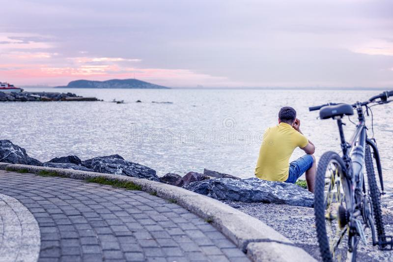 Cyclist sits on the beach at sunset stock photography