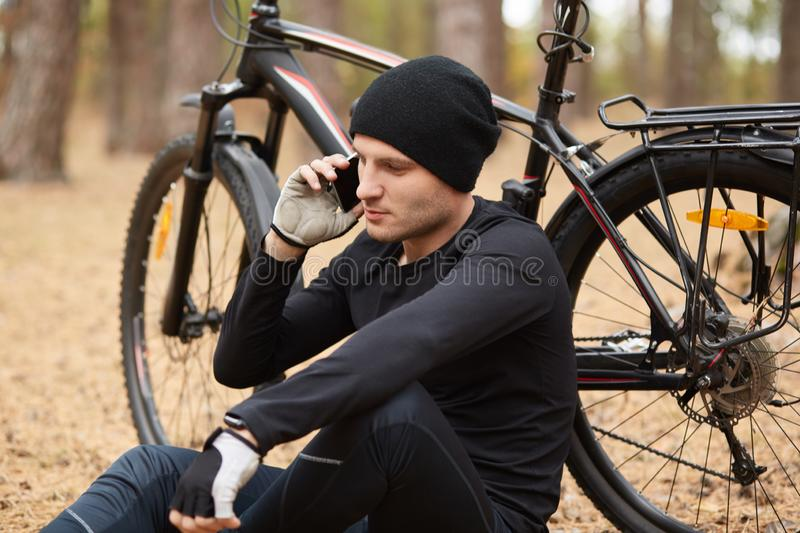 Cyclist sitting on ground, holding smartphone in one hand, having conversation over his mobile phone, leaning on bicycle, relaxing royalty free stock photography
